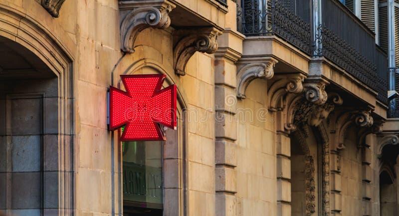 Röda korset av ett catalonia apotek på en sommardag royaltyfri fotografi
