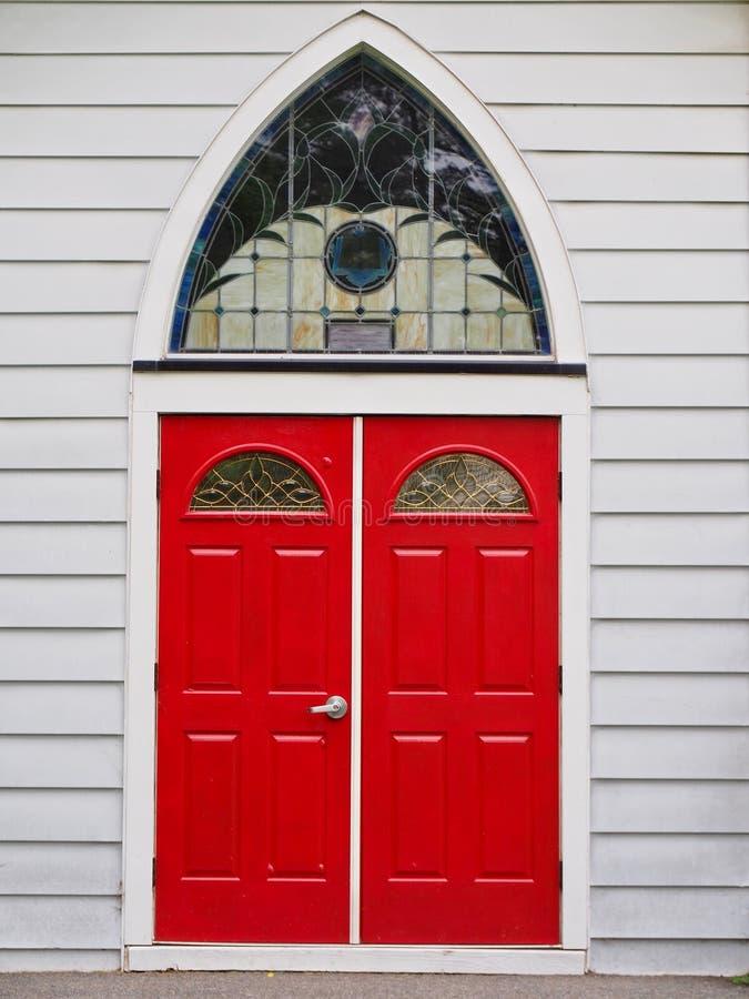 Röda kyrkliga dörrar med Reuleaux välva sig fönstret royaltyfri fotografi