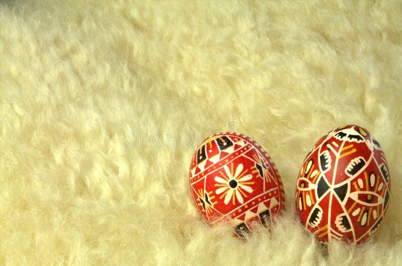 Röda mönstrade påskägg på fårskinn royaltyfria bilder