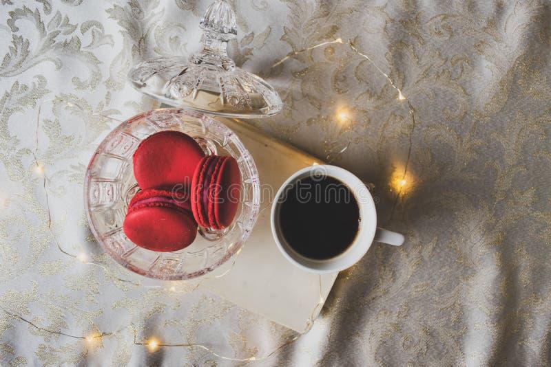 Röda macarons i kristallbunke, bok och ett kaffe arkivbild