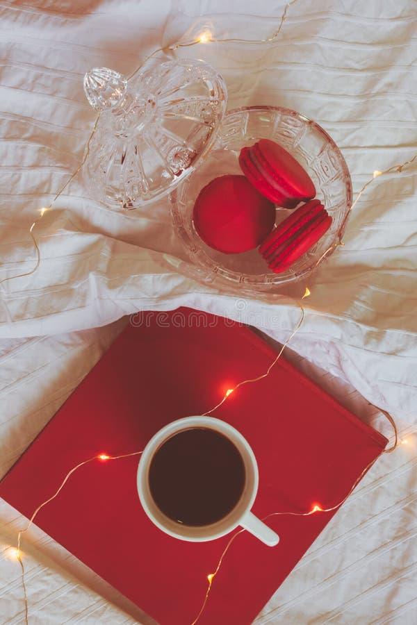 Röda macarons i kristallbunke, bok och ett kaffe arkivfoto