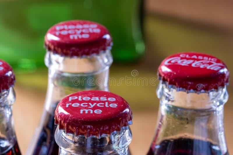 Röda metalllock på överkanten av den retro stilcocaen - colaflaskor som bär meddelandet 'Please, återanvänder mig ', royaltyfri foto