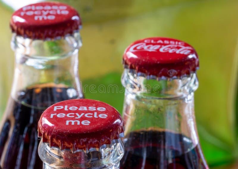 Röda metalllock på överkanten av den retro stilcocaen - colaflaskor som bär meddelandet 'Please, återanvänder mig ', fotografering för bildbyråer