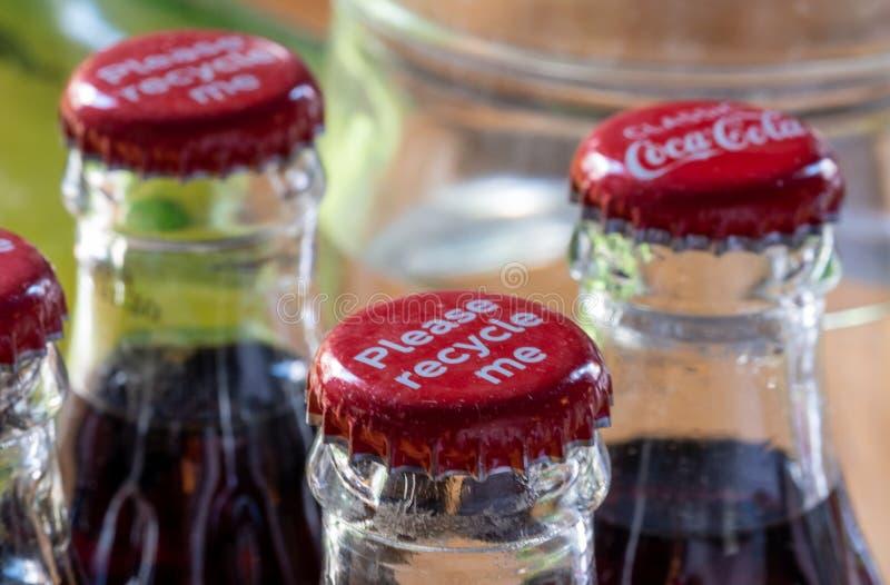 Röda metalllock på överkanten av den retro stilcocaen - colaflaskor som bär meddelandet 'Please, återanvänder mig ', royaltyfri bild