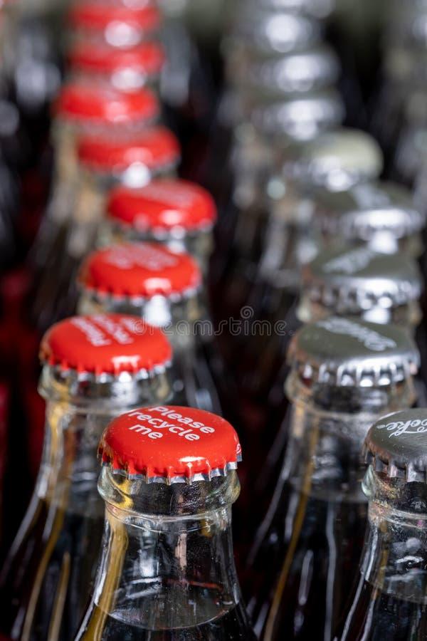 Röda metalllock på överkanten av den retro stilcocaen - colaflaskor som bär meddelandet 'Please, återanvänder mig ', royaltyfri fotografi