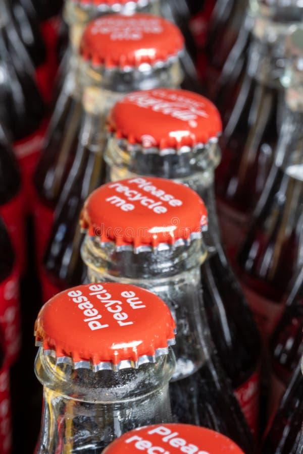 Röda metalllock på överkanten av den retro stilcocaen - colaflaskor som bär meddelandet 'Please, återanvänder mig ', arkivbild