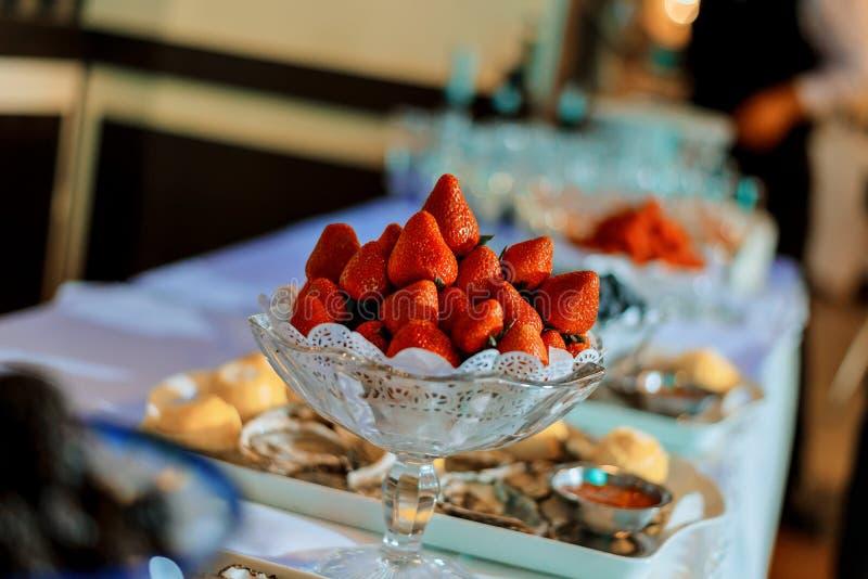 Röda mogna jordgubbar i en exponeringsglasbunke på den vita tabellen arkivbilder