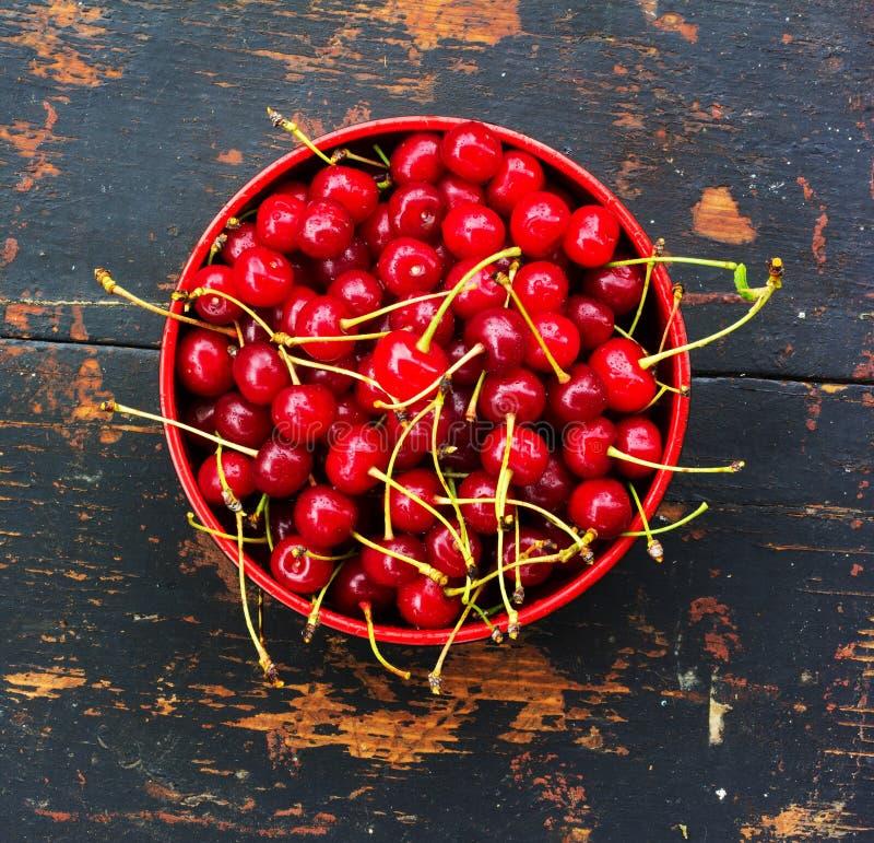 Röda mogna körsbär med svansar i en rund platta på en gammal svart träbakgrund med en spricka fotografering för bildbyråer