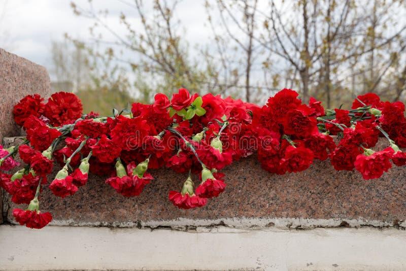 Röda nejlikor ligger på den granit- gravstenen i Victory Memorial fotografering för bildbyråer