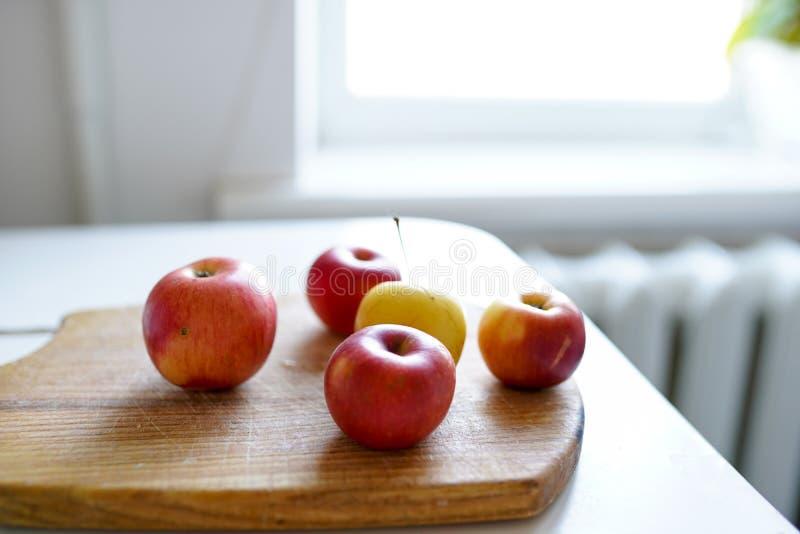 Röda nya äpplen på träbrädet på ljus bakgrund i vitt kök sund mat royaltyfria foton