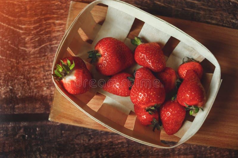 Röda nya jordgubbar i ecokorgen som tonas arkivfoton