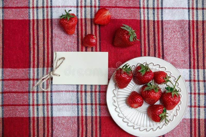 Röda nya jordgubbar på den keramiska plattan, på kontrollbordduken Önskakort Organisk sund smaklig mat för frukost Matlagning Vit royaltyfri bild
