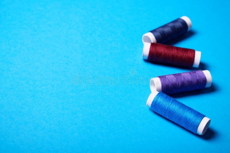 Röda och blåa sy trådar arkivfoton
