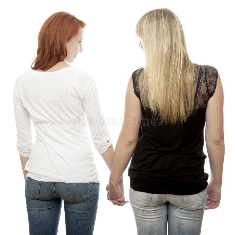 Röda och blonda haired flickor som rymmer händer tillbaka arkivfoto