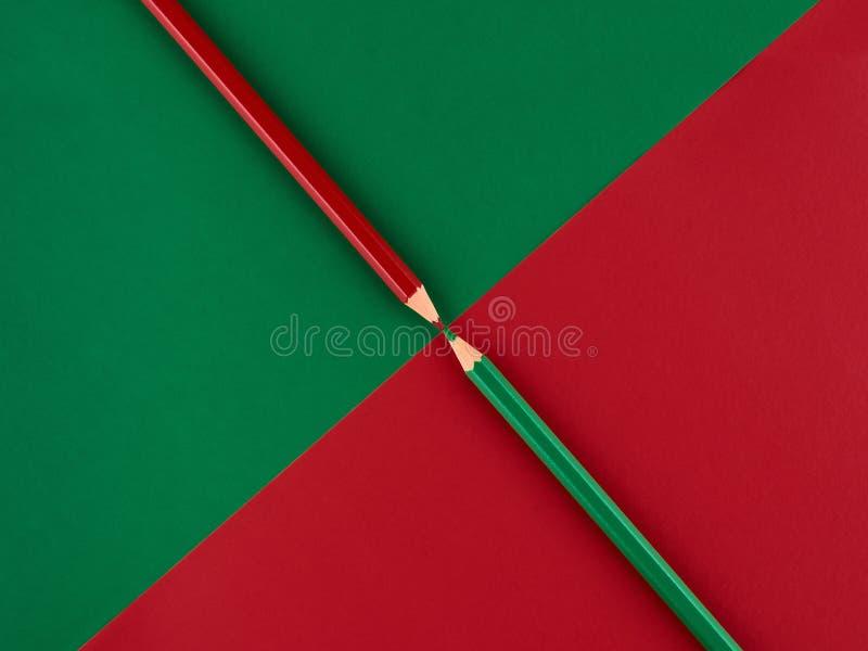 Röda och gröna blyertspennor på en kontrastera bakgrund royaltyfri foto
