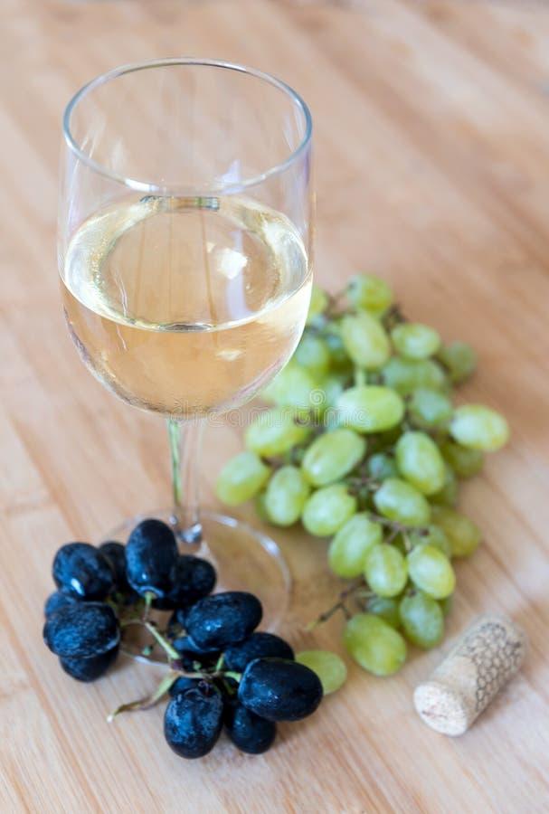 Röda och gröna druvafrukter och vitt vin royaltyfria bilder