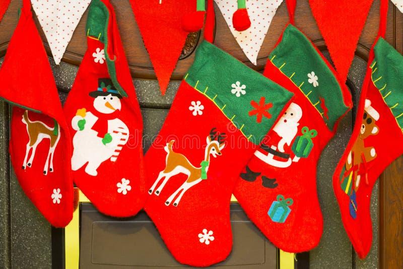 Röda och gröna julstrumpor med snögubben, santa och hjortar arkivbilder