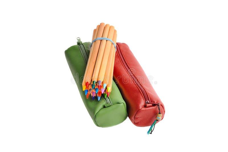 Röda och gröna muffar med färgblyertspennor royaltyfri foto