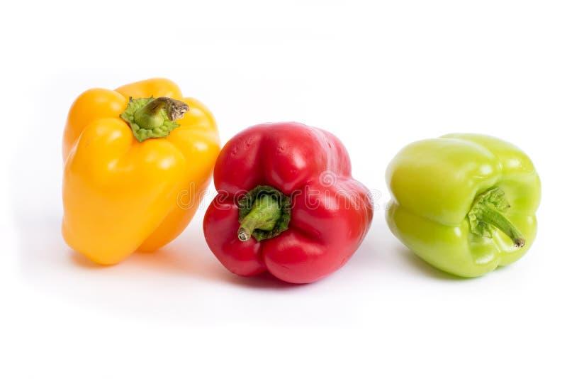 Röda och gröna söta peppar på en vit bakgrund Mångfärgade grönsaker i sammansättningen Röda och gröna söta peppar på en wh arkivfoto