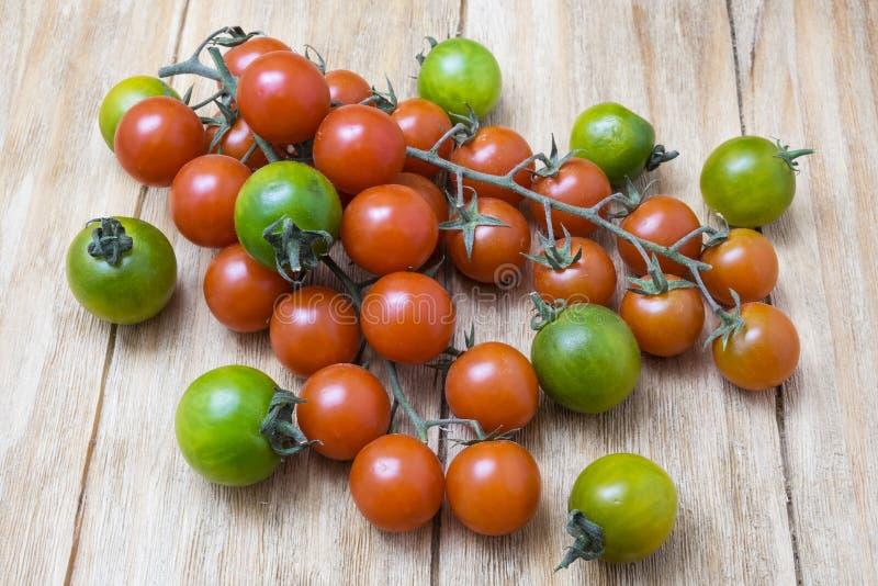 Röda och gröna tomater på filial royaltyfri foto