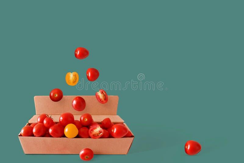 Röda och gula nya körsbärsröda tomater i en kartong på en grön bakgrund Collage av nya grönsaker idérik bild arkivfoton