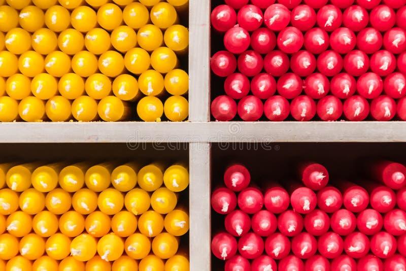 Röda och gula stearinljus på hyllor shoppar in royaltyfri fotografi