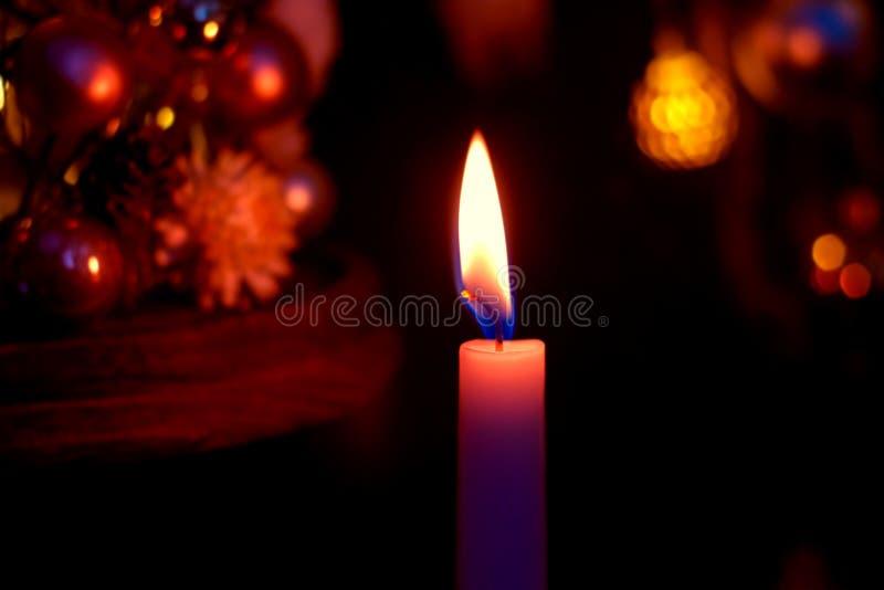 Röda och guld- julbollar på ett julträd med en sikt för stearinljusljuscloseup i en låg tangent med ett kopieringsutrymme royaltyfria bilder