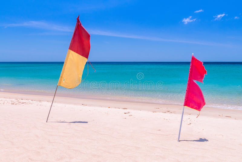 Röda och guling-röda flaggor på den tomma stranden royaltyfri fotografi