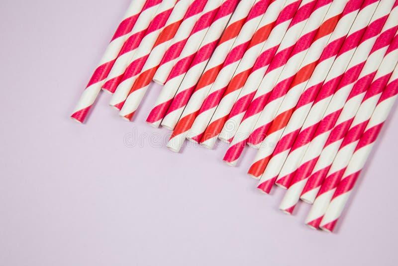 Röda och orange sugrör på den rosa bakgrunden arkivfoto