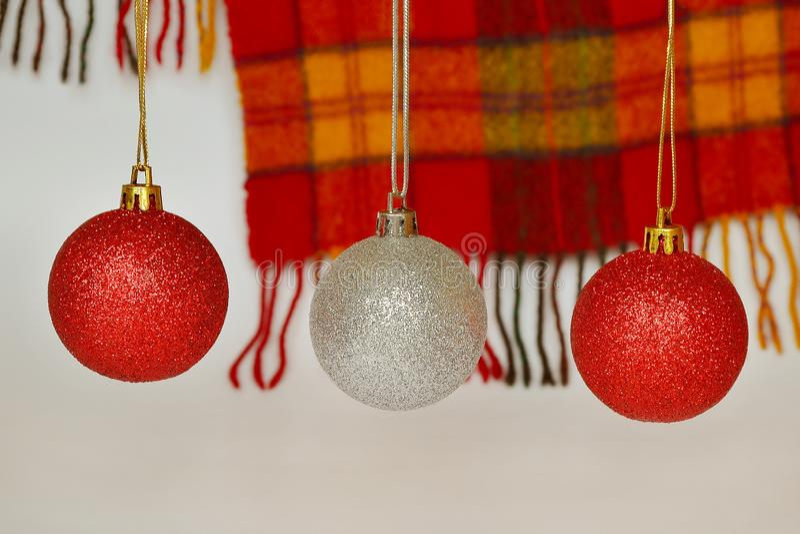 Röda och silverjulbollar mot en woolen röd och gul rutig halsduk med en frans Begrepp av ferier, jul och N arkivfoton