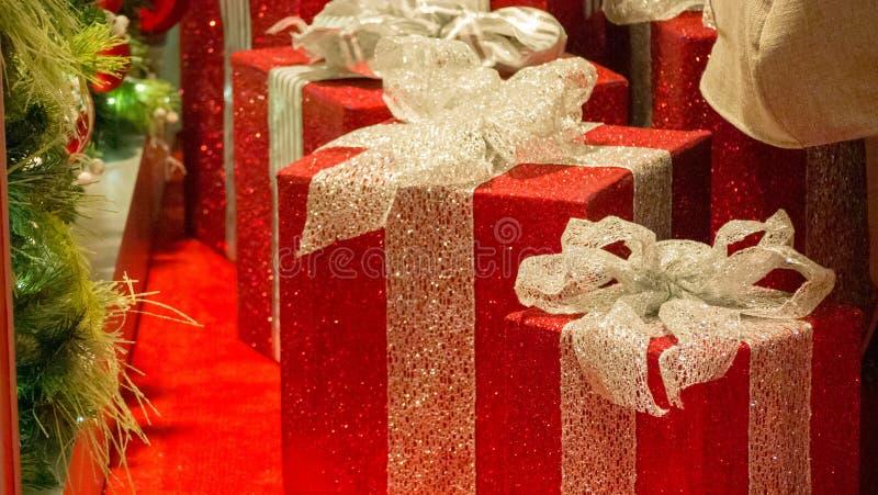 Röda och silverjulgåvor med trädet i mitt av ramen royaltyfri foto