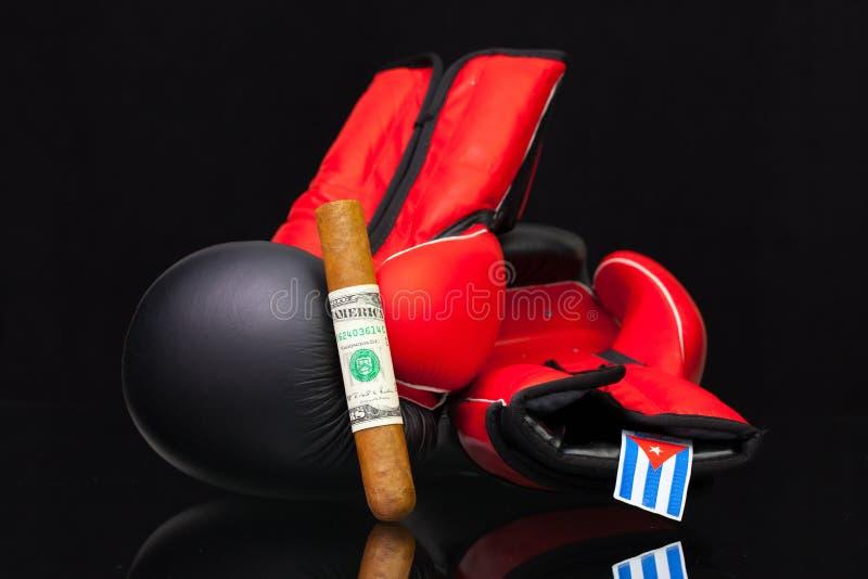 Röda och svarta boxninghandskar och lyxiga kubanska cigarrer arkivfoto