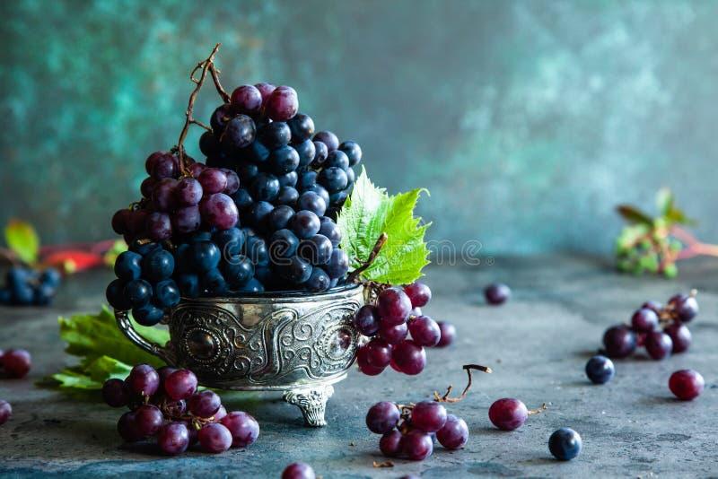 Röda och svarta druvor med druvasidor i en metall bowlar på en rost arkivfoton