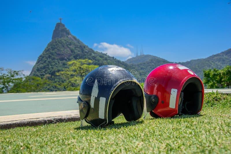 Röda och svarta motorcykelhjälmar som ligger på gräset på bakgrunden av statyn av Kristus Förlossare arkivbilder