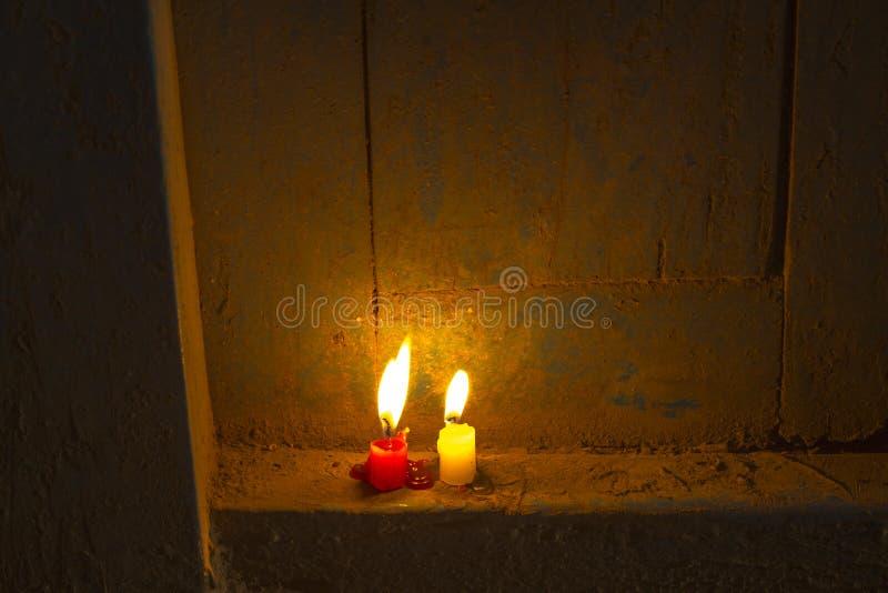 Röda och vita glödande unburned stearinljus på en trädörr på natten arkivfoto