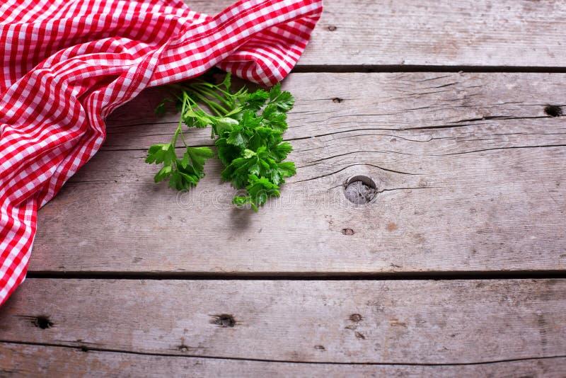 Röda och vita kökshandduk- och gräsplanpersiljasidor på lantligt arkivfoto