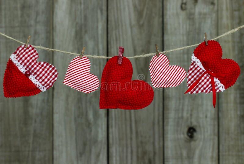 Röda och vita landstyghjärtor som hänger på klädstreck vid det wood staketet arkivbilder