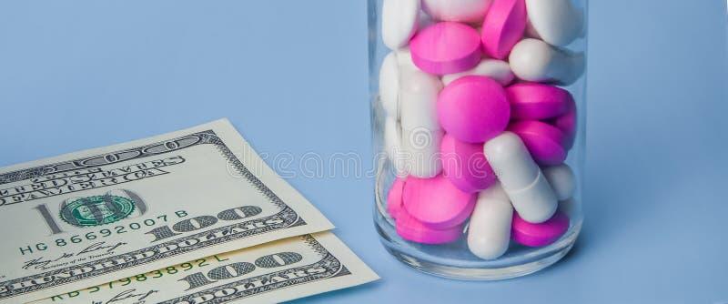 Röda och vita preventivpillerar i glasflaska på blå bakgrund royaltyfria foton