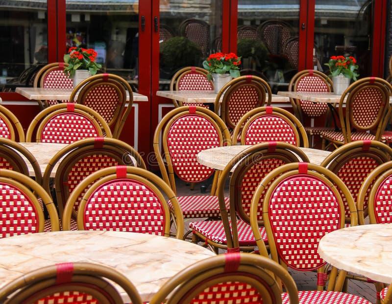 Röda och vita vide- stolar och små tabeller i utomhus- kafé royaltyfri foto
