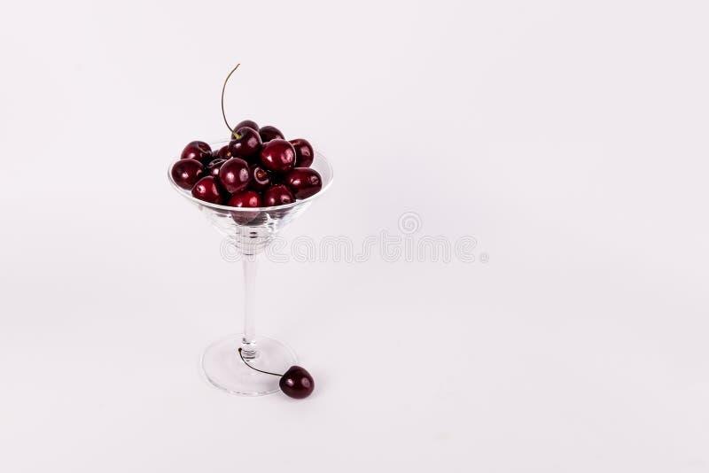 Röda organiska söta körsbär i martini exponeringsglas på vit bakgrund royaltyfria foton