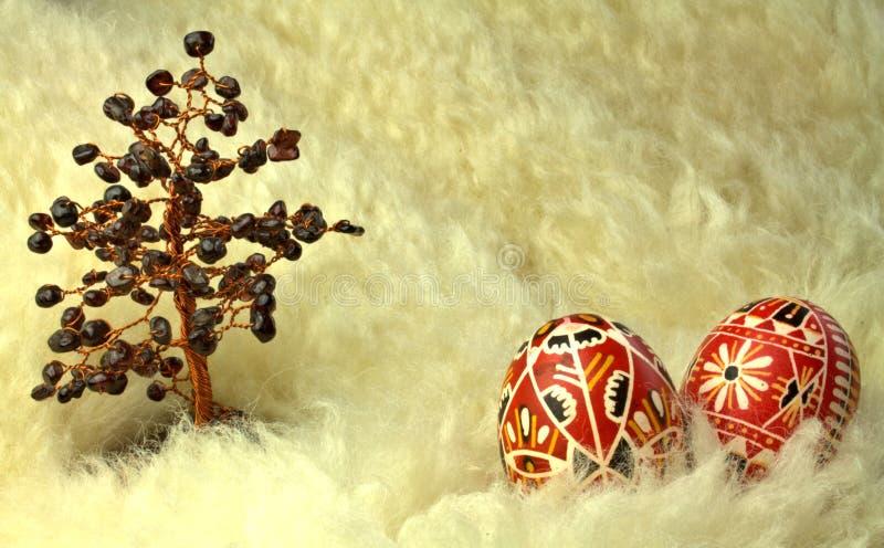 Röda påskägg och granatröttträd på fårskinn royaltyfri foto