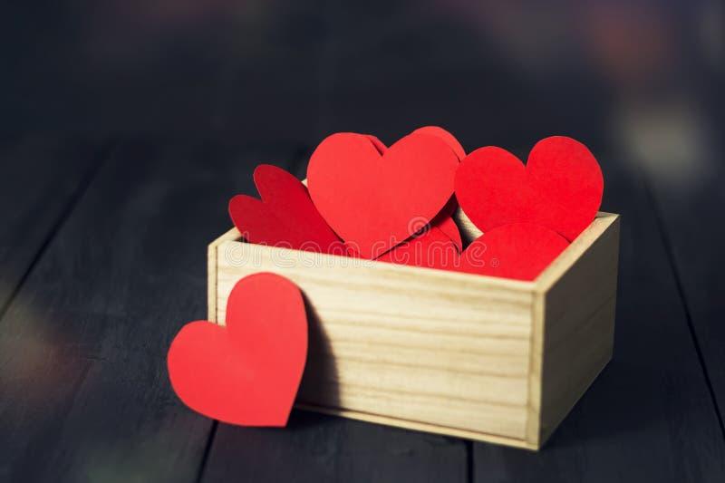 Röda pappers- hjärtor i en träask mörkt trä för bakgrund kopiera avstånd St Dag för valentin` s royaltyfria foton
