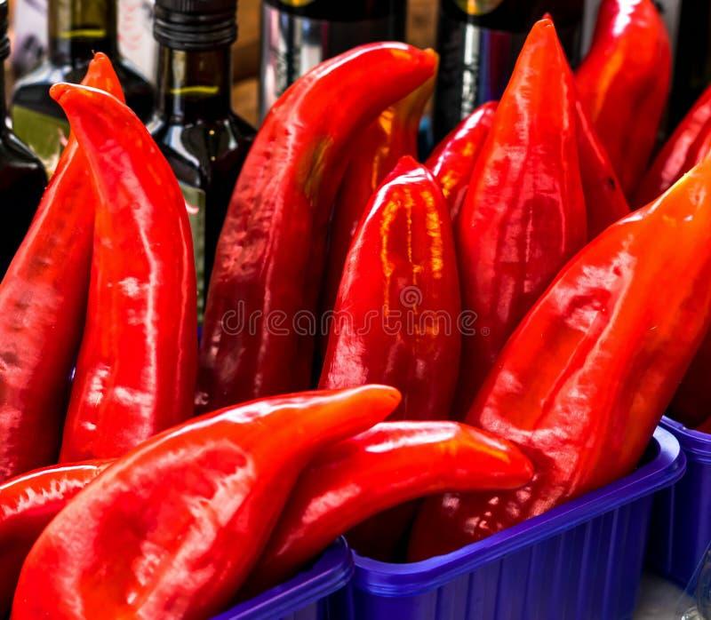 Röda peppar på stadsgatamarknad arkivfoto