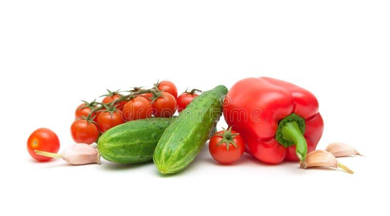Röda peppar, vitlök, körsbärsröda tomater och gurkor på en vit b arkivfoto