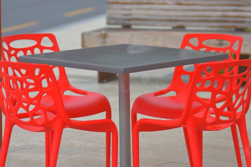 R?da plast- utomhus- stolar royaltyfri foto
