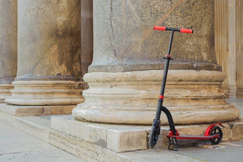Röda pushsparkcyklar mot bakgrunden av kolonnadpanteon i Romaen, Italien royaltyfria bilder