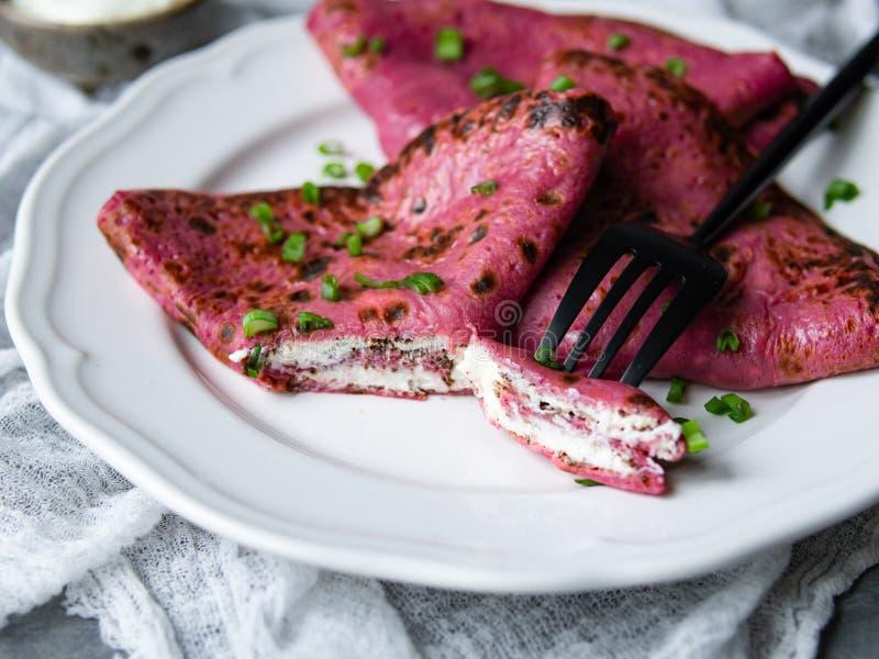 Röda rödbetapannkakor, rosa tunna betakräppar som stoppas med gräddost, och salladslökar på grå bakgrund Shrovetide Maslenitsa arkivbilder