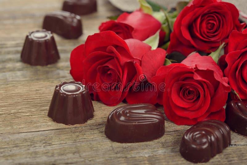 Röda ro och choklader arkivfoton