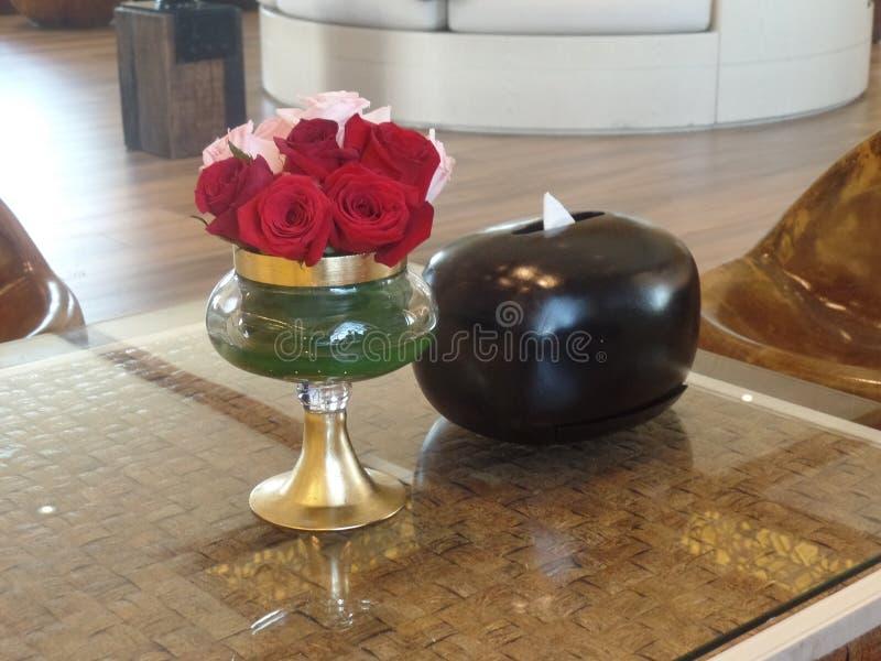 Röda rosor i en vas på mottagandet arkivfoton
