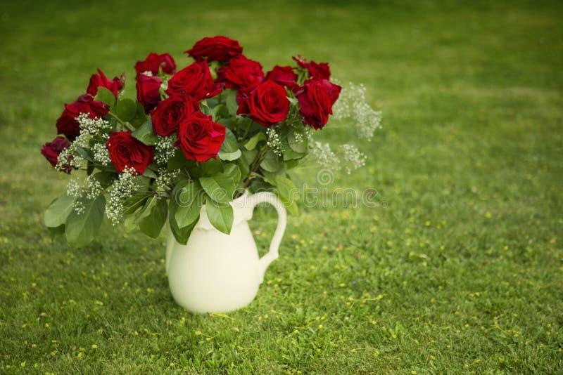 Röda rosor i vas på gräsmatta arkivfoto